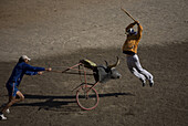 A bullfighter practices stabbing banderillas behind a stuffed bull's head mounted on a bicycle wheel pushed by another bullfighter in the ring in Apizaco, Tlaxcala, Mexico, October 1, 2008.