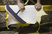 A worker holds the large blade which he uses to file down the rough side of yellow dyed sheep skins at the Berber leather tannery in Fes El-Bali, Morocco, on October 31, 2007.