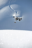 Skifahrer macht Bachflip über kleines Kliff in großer Schneefläche, Hochfügen, Zillertal, Österreich
