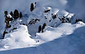 Skier skiing down into a gorge full of snow, Hochfuegen, Zillertal, Austria