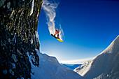 Snowborder macht Backflip über hohes Kliff und steht kopfüber in der Luft, Hochfügen, Zillertal, Österreich