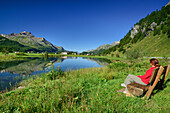 Woman sitting on a bench with view over Inn river to Sils-Baselgia, Sils, Upper Engadin, Engadin, Canton of Graubuenden, Switzerland