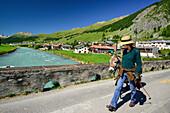 Woman walking a donkey over a bridge, S-chanf, La Plaiv, Upper Engadin, Canton of Graubuenden, Switzerland