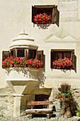 Windows with geraniums of an Engadin house, Guarda, Lower Engadin, Canton of Graubuenden, Switzerland