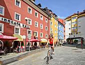 Cyclist passing a cafe, Kufstein, Tyrol, Austria