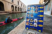 Man paddling past a fast food menu, Murano, Venice, Italy