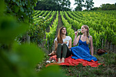 Two young women enjoying a white wine in vineyard above Weingut am Stein winery (MR), Wuerzburg, Franconia, Bavaria, Germany