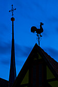 Silhouette of rooftop rooster ornament and church tower at dusk, Frickenhausen, near Ochsenfurt, Franconia, Bavaria, Germany