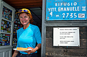 Woman standing with cake in her hands at Rifugio Vittorio Emanuele II, Gran Paradiso, Gran Paradiso Nationalpark, Graian Alps range, valley of Aosta, Aosta, Italy