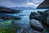 Rocky shores of Gjogv, looking towards the mountains of Kalsoy, Faroe Islands, Denmark, Europe
