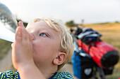 Boy (4 years) drinking from a bottle of water, Marielyst, Falster, Denmark
