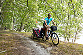 Cyclist with child trailer passing a forest path, Naesgaard, Falster, Denmark