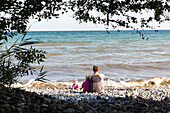Mother and children (1-4 years) sitting at Baltic Sea beach, Klintholm, Mon island, Denmark