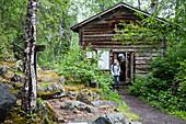Hiker in front of hut Taivalkoengas, Karhunkierros hiking trail, Oulanka National Park, Northern Ostrobothnia, Finland