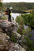 Female hiker at midnight on the rock cliff Ristikallio, Karhunkierros, Oulanka National Park, Northern Ostrobothnia, Finland
