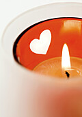 Lit candle in candleholder with heart pattern