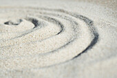 Spiral shape drawn in sand, close-up, surface level