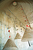 Spirals of incense hanging from ceiling