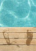 Wet footprints by edge of swimming pool