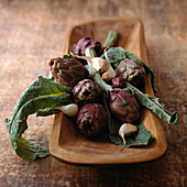 Purple artichokes with leaves and garlic cloves in wooden container, close-up