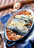 Mackerel in casserole dish with vegetables, close-up