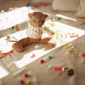 Stuffed teddy bear on floor with party favors
