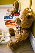 Teddy bears sitting on floor with several pairs of child's shoes