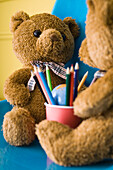 Teddy bears seated face to face with cup of colored pencils between them