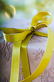Wrapped gift tied with gold ribbon, close-up