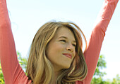 Young woman raising arms outdoors, smiling