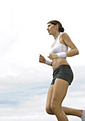 Young woman jogging, low angle view