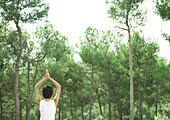 Woman standing in sun salutation, facing trees