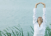 Woman stretching arms over head, lake in background