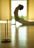 Woman doing cobra pose, side view, focus on incense in foreground