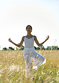Woman doing yoga pose in field