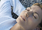 Woman lying on gravel with hands behind head, eyes closed, close-up