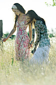 Two young women standing in field