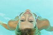 Young woman in pool, smiling at camera, view from directly above