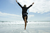 Businesswoman barefoot on beach, jumping into the air, rear view