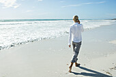 Woman walking barefoot on beach, using cell phone, rear view