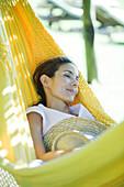 Woman resting in hammock, holding straw hat