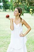 Woman balancing apple on palm of hand, smiling