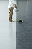 Man watering tray of wheatgrass