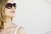 Woman wearing sunglasses, looking away, portrait