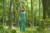 Young woman stretching in woods