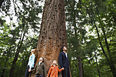 Family standing together at base of tall tree, holding hands