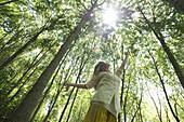 Young woman standing in woods, reaching toward sun shining through canopy