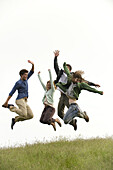 Young adults jumping on meadow