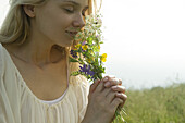 Young woman smelling bouquet of wildflowers, cropped