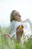 Barefoot young woman sitting in grass, holding dandelion flower between toes